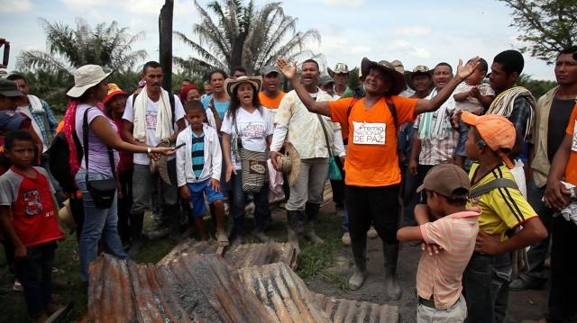 Orlando Ospino, miembro de la comunidad de Las Pavas canta delante a los restos de un rancho quemado por órdenes de la empresa palmera Aportes San Isidro